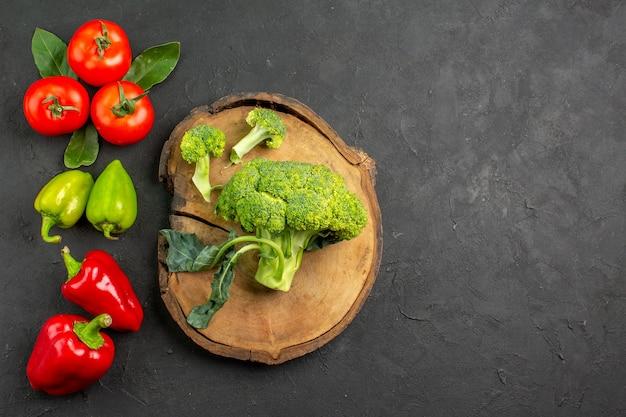 Vue de dessus du brocoli frais avec des tomates et des poivrons sur une salade mûre de table sombre