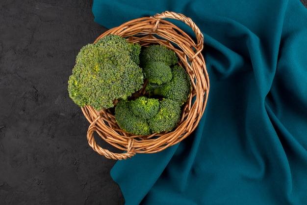 Vue de dessus du brocoli vert frais à l'intérieur du panier sur le fond gris