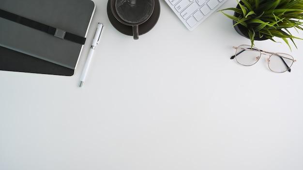 Vue de dessus du bureau blanc avec clavier, plante d'intérieur, lunettes, cahier, tasse à café et espace de copie.