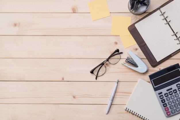 Vue de dessus du bureau en bois avec outils de bureau et plante