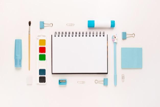 Vue de dessus du bureau de bureau bleu blanc moderne avec fournitures scolaires et papeterie sur table autour d'un espace vide pour le texte. retour au concept de l'école à plat avec maquette