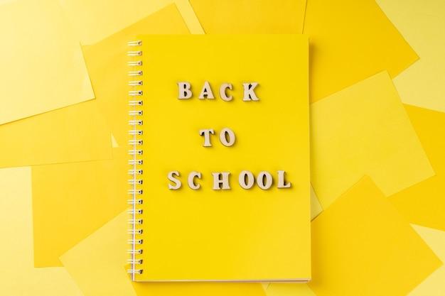 Vue de dessus du bureau de bureau jaune vif moderne avec bloc-notes jaune. retour au concept de l'école