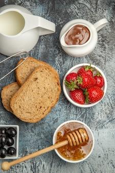 Vue de dessus du bureau du petit déjeuner pain miel et thé sur un sol sombre matin nourriture thé