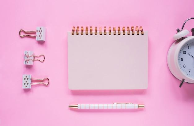 Vue de dessus du bureau féminin avec cahier vierge et réveil