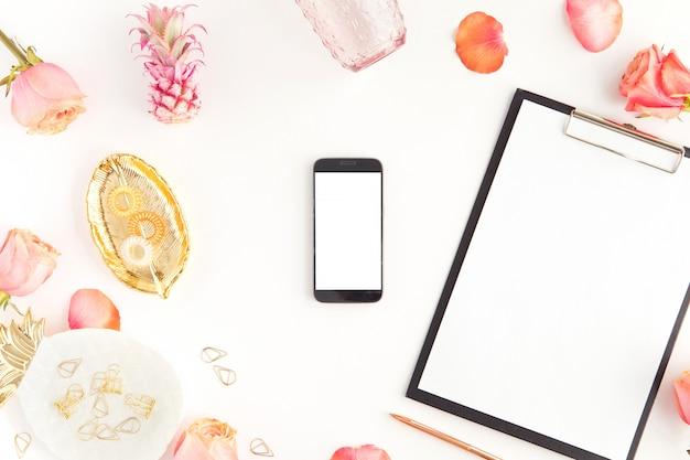 Vue de dessus du bureau féminin avec écran blanc téléphone mobile et tablette, fleurs roses roses, plaque comme feuille et ananas isolé on white