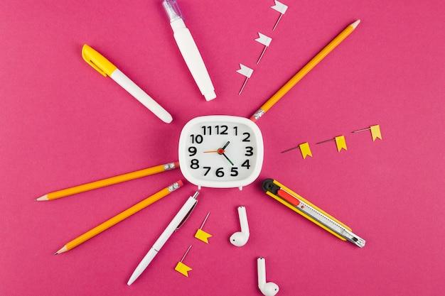 Vue de dessus du bureau avec horloge et une variété de stylos et crayons