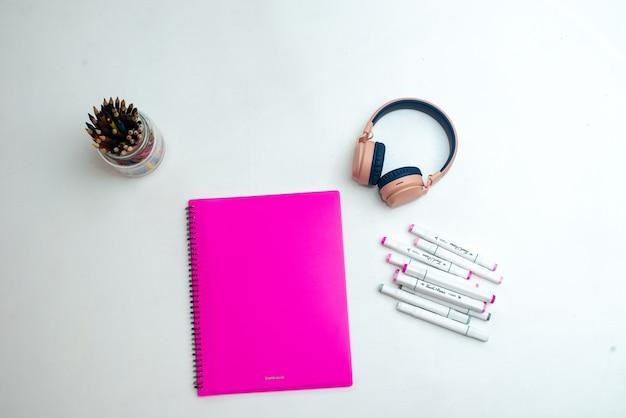 Vue de dessus du bureau. marqueurs multicolores professionnels, dossier rose, écouteurs