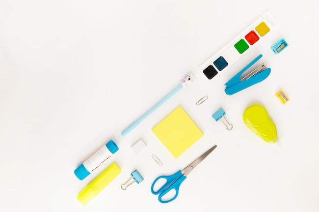 Vue de dessus du bureau moderne blanc, bleu, jaune avec fournitures scolaires et papeterie sur table autour d'un espace vide en diagonale pour le texte. retour au concept de l'école à plat avec maquette