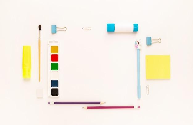 Vue de dessus du bureau moderne blanc, bleu, jaune avec fournitures scolaires et papeterie sur table autour d'un espace vide pour le texte. retour au concept de l'école à plat avec maquette