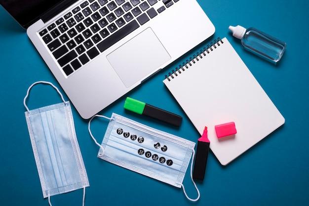 Vue de dessus du bureau avec ordinateur portable et masques médicaux