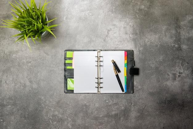 Vue de dessus du bureau avec une plante en pot et un cahier
