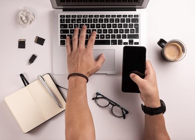 Vue de dessus du bureau pour photographe ou designer, avec ordinateur, table, café, ordinateur portable, téléphone portable, cartes mémoire