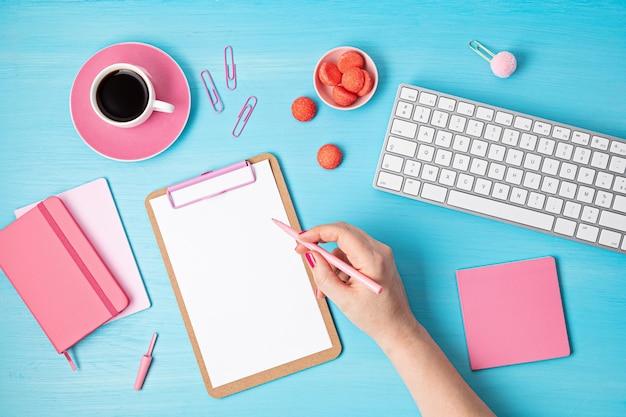 Vue de dessus du bureau. table avec clavier, presse-papiers et fournitures de bureau en rose. espace de travail de bureau à domicile plat, travail à distance, apprentissage à distance, vidéoconférence, idée d'appels