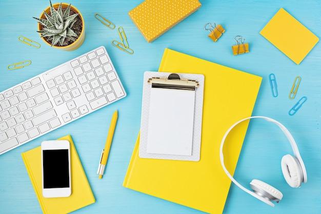 Vue de dessus du bureau. table avec clavier, smartphone, presse-papiers et fournitures de bureau. espace de travail de bureau à domicile plat, travail à distance, apprentissage à distance, vidéoconférence, idée d'appels