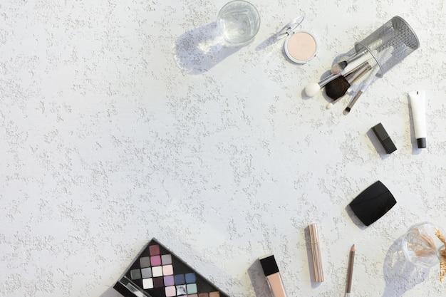 Vue de dessus du bureau de travail de femme beauté blogger avec ordinateur portable, ordinateur portable, cosmétique décorative, fleurs, enveloppe sur une table en pastel blanche twxtured. fond plat avec des ombres et des lumières