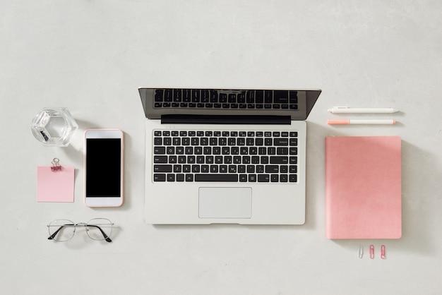 Vue de dessus du bureau de la travailleuse avec ordinateur portable, fleurs et autres articles