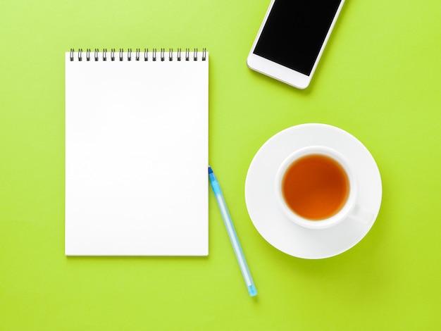 Vue de dessus du bureau vert clair moderne avec bloc-notes vide, tasse de thé