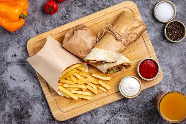Vue de dessus du burrito de boeuf avec jalapeno de laitue de concombre de tomate servi avec des frites et des sauces