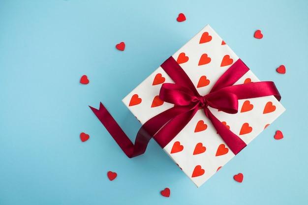 Vue de dessus du cadeau avec arc rouge et petits coeurs rouges sur fond bleu