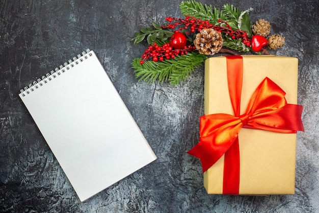 Vue de dessus du cadeau du nouvel an avec ruban rouge et décorations d'accessoires et cahier sur une surface sombre