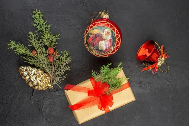 Vue de dessus du cadeau de noël en papier brun attaché avec des ornements d'arbre de noël en ruban rouge sur une surface sombre
