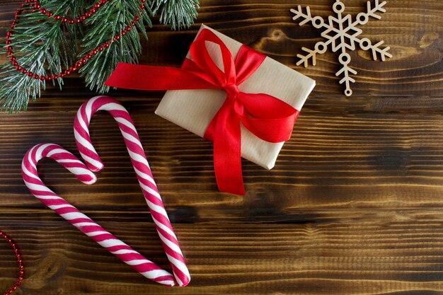 Vue de dessus du cadeau avec ruban rouge et composition de noël sur la table en bois
