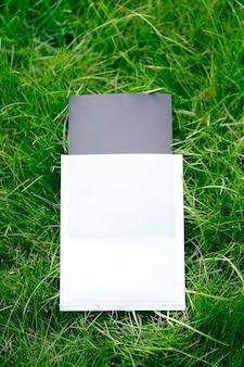 Vue de dessus du cadre carré, une mise en page créative faite d'herbe verte avec un étui noir et blanc pour les étiquettes de vêtements. le formulaire pour la carte d'invitation