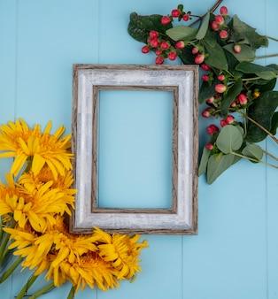 Vue de dessus du cadre avec des fleurs autour sur bleu avec espace copie