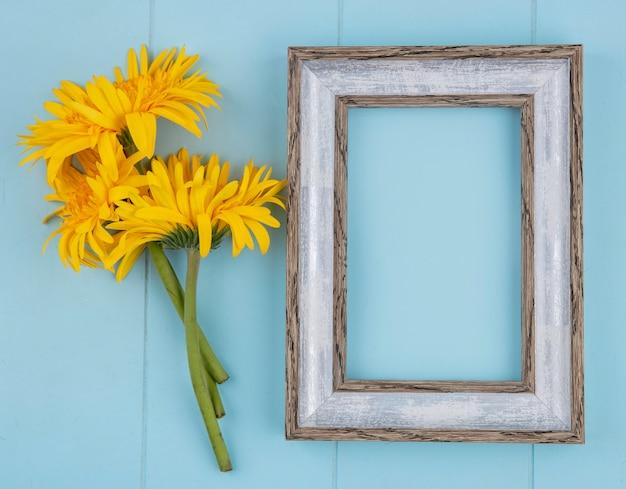 Vue de dessus du cadre avec des fleurs sur fond bleu avec espace copie