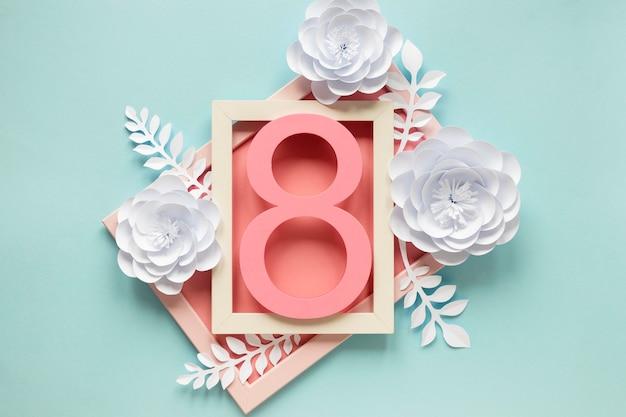 Vue de dessus du cadre avec des fleurs en papier et date pour la journée de la femme