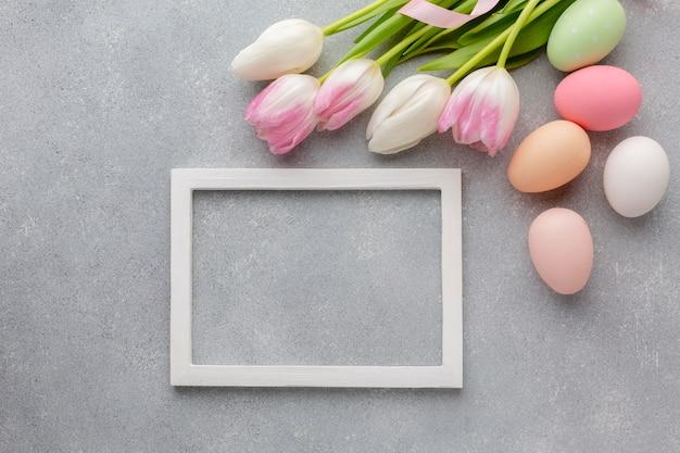 Vue de dessus du cadre avec des oeufs de pâques colorés et de belles tulipes