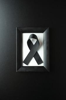 Vue de dessus du cadre photo avec un arc noir sur un mur sombre