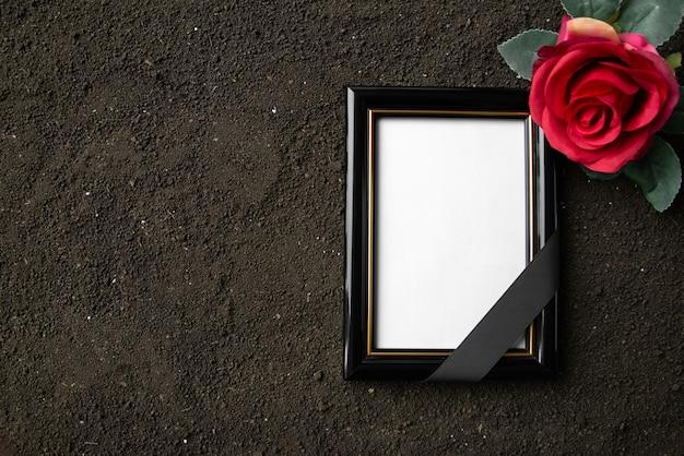 Vue de dessus du cadre photo avec fleur rouge sur sol sombre