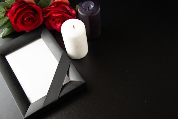 Vue de dessus du cadre photo avec des fleurs rouges et des bougies sur une surface sombre