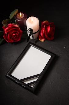 Vue de dessus du cadre photo avec des fleurs rouges sur un mur sombre