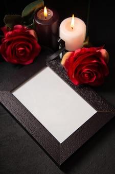 Vue de dessus du cadre photo avec des fleurs rouges sur une surface sombre