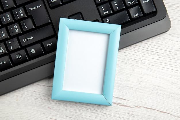 Vue de dessus du cadre photo vide bleu sur un ordinateur portable à moitié tourné sur blanc
