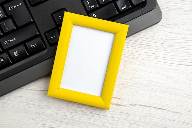 Vue de dessus du cadre photo vide jaune sur un ordinateur portable à moitié tourné sur blanc dépouillé