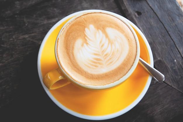 Vue de dessus du café d'art de latte avec une tasse de café de couleur jaune