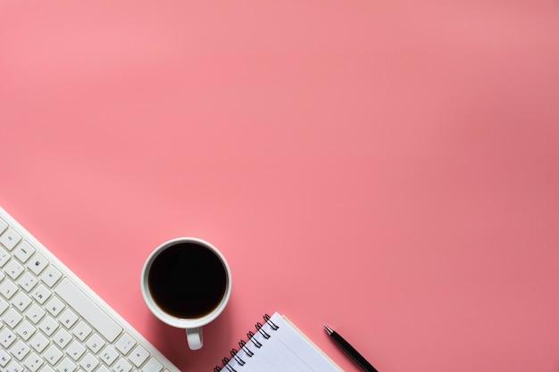 Vue de dessus du café avec un cahier et autres fournitures sur fond rose et fond