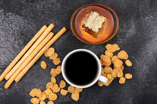 Vue de dessus du café avec des craquelins et du miel sur une surface noire horizontale