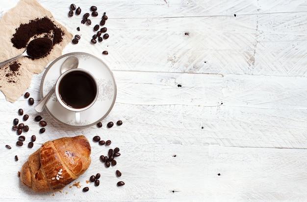 Vue de dessus du café avec croissant sur bois blanc rustique