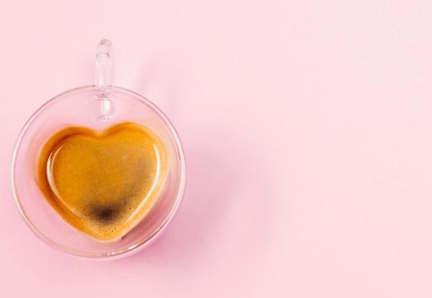 Vue de dessus du café dans une tasse en verre en forme de coeur rose
