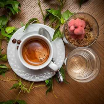 Vue de dessus du café expresso avec de l'eau et une branche de raisin et une cuillère dans une tasse