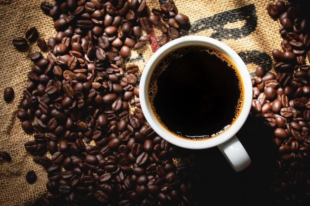 Vue de dessus du café noir dans une tasse à café en céramique blanche avec du café torréfié