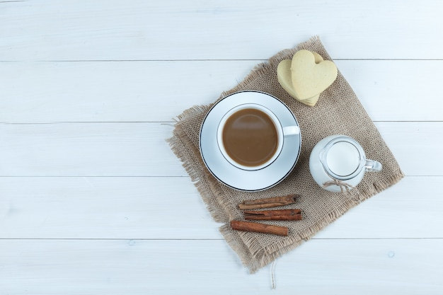 Vue De Dessus Du Café En Tasse Avec Des Biscuits, Des Bâtons De Cannelle, Du Lait Sur Du Bois Et Un Morceau De Fond De Sac. Photo gratuit
