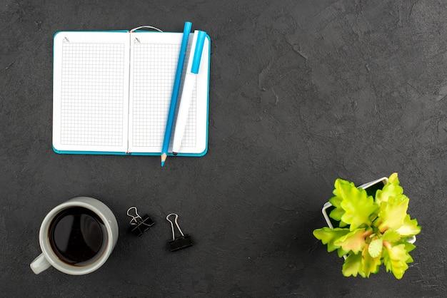 Vue de dessus du cahier bleu ouvert et stylo une tasse avec un pot de fleur de café sur fond noir