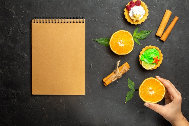 Vue de dessus du cahier de délicieux biscuits citrons verts à la cannelle et oranges à moitié coupées avec des feuilles sur fond sombre