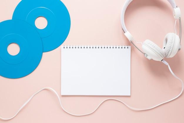 Vue de dessus du cahier de disques et des écouteurs sur backgroung rose