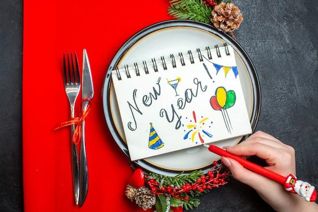 Vue de dessus du cahier avec l'écriture du nouvel an et des dessins sur une assiette avec des accessoires de décoration des branches de sapin et des couverts sur une serviette rouge